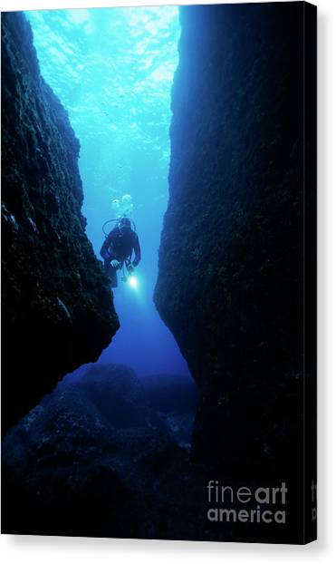 Underwater Caves Canvas Print - One Scuba Diver Shines An Underwater Light While Swimming Through A Cave by Sami Sarkis