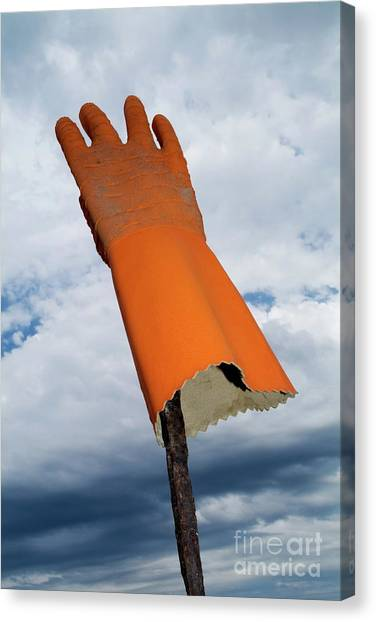 Protective Clothing Canvas Print - Orange Rubber Glove On A Wooden Post Against A Cloudy Sky by Sami Sarkis