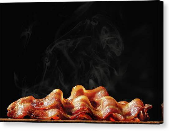 Bacon Canvas Print - Pile Of Sizzling Bacon Isolated On Black by Susan Schmitz
