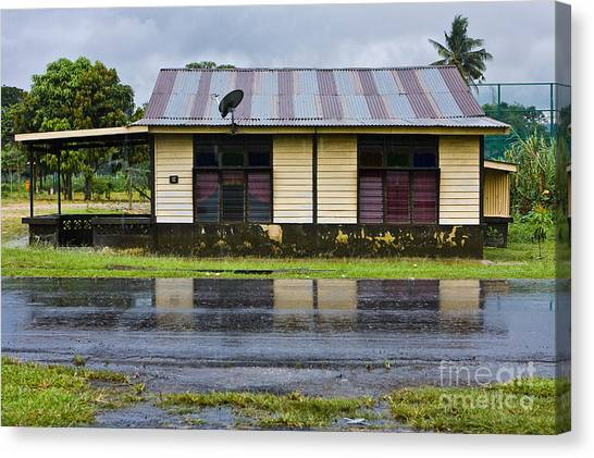 rainy day in a Malaysian kampung Canvas Print by John Buxton