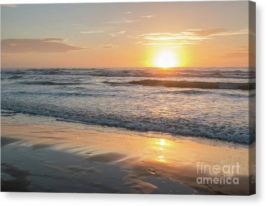 Rising Sun Reflecting On Wet Sand With Calm Ocean Waves In The B Canvas Print