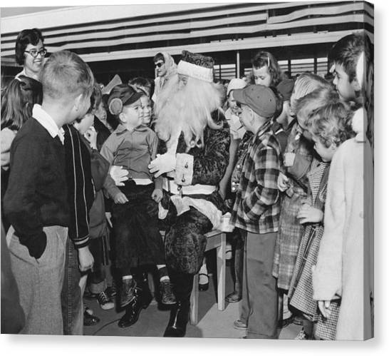 Elementary School Canvas Print - Santa Surrounded By Children by Underwood Archives