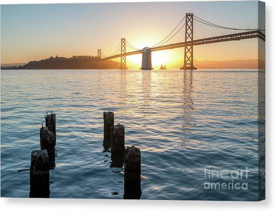 Six Pillars Sticking Out The Water With Bay Bridge In The Backgr Canvas Print