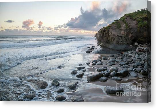 Sunset View In The Distance With Large Rocks On The Beach Canvas Print