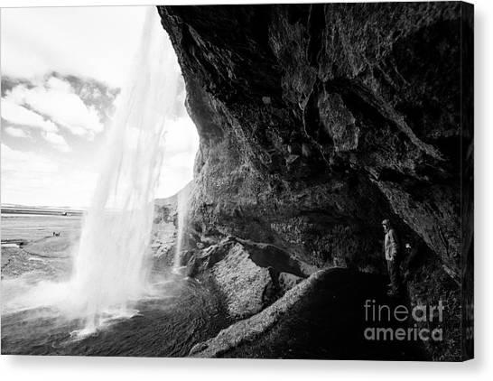 Seljalandsfoss Canvas Print - tourists on walking path behind Seljalandsfoss waterfall iceland by Joe Fox