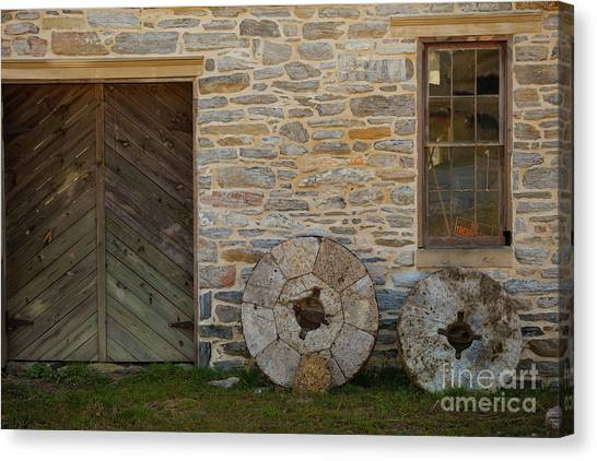 Two Mill Stones Against Building Canvas Print