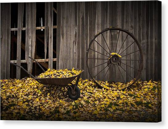 Wheel Barrow Canvas Print - Wagon Wheel Rim And Wheel Barrel Covered With Fallen Autumn Leaves by Randall Nyhof