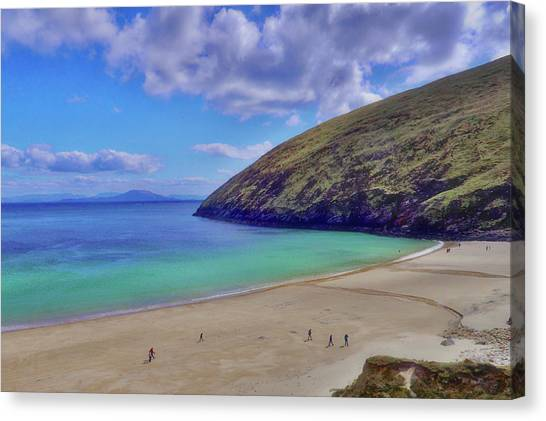 Walkers On Keem Beach, Achill Island Feted By The Green Atlantic Ocean. Canvas Print by Paul Mc Namara