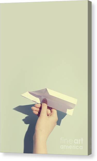 Paper Planes Canvas Print - Woman's Hand Playing With White Paper Plane by Michal Bednarek