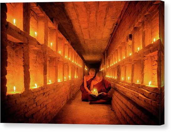 Young Buddhist Monk Are Reading A Book With Light From Candle  Canvas Print by Anek Suwannaphoom