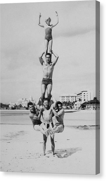 Men And Girl Perform Acrobatics On Beach Canvas Print