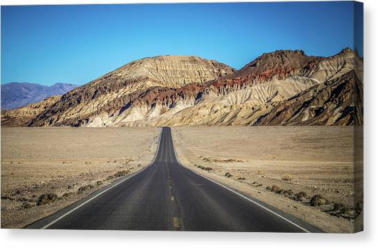 Canvas Print featuring the photograph Lonely Road In Death Valley National Park In California by Alex Grichenko