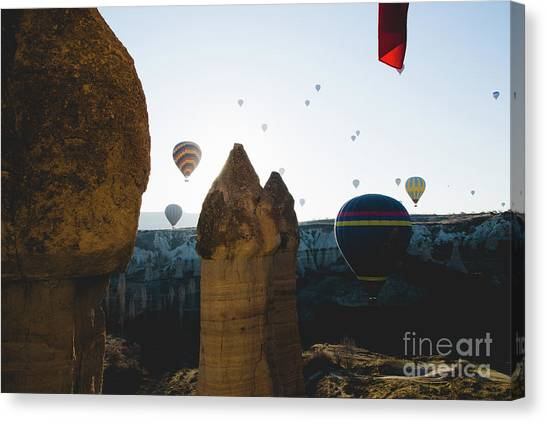 hot air balloons for tourists flying over rock formations at sunrise in the valley of Cappadocia. Canvas Print