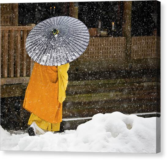 A Buddhist Monk Walks Through A Snow Canvas Print by Mint Images - Art Wolfe