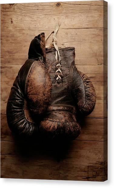 A Pair Of Worn Old Boxing Gloves On Canvas Print by The flying dutchman