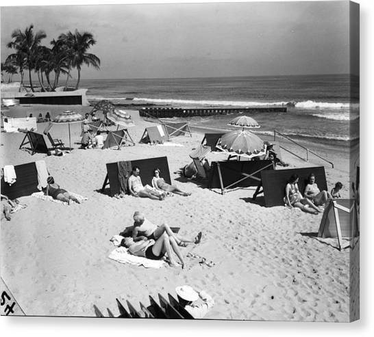 A View Of Sunbathers Lying On A Beach Canvas Print