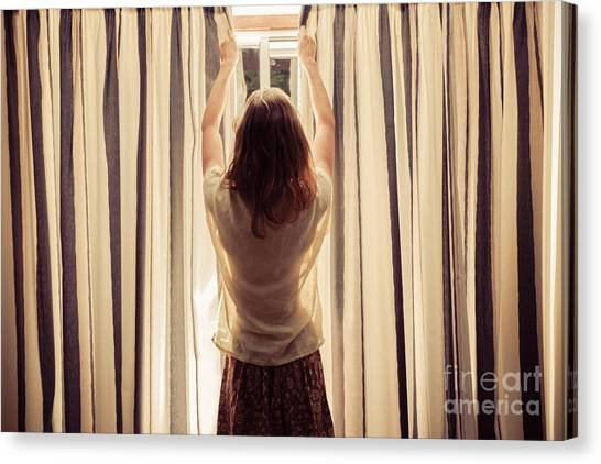 Indoors Canvas Print - A Young Woman Is Opening The Curtains by Lolostock