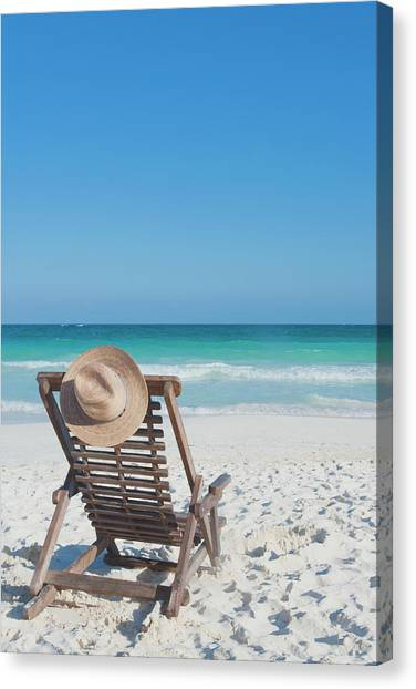 Beach Chair With A Hat On An Empty Beach Canvas Print