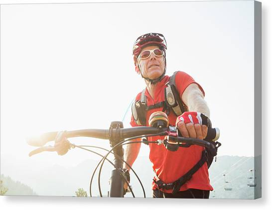 Caucasian Man Pushing Mountain Bike Canvas Print by Mike Kemp