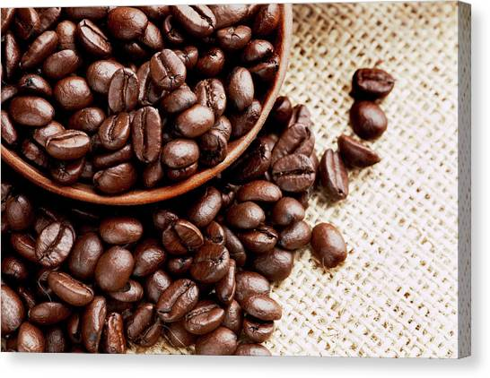 Coffee Beans Spilling From Wooden Bowl Canvas Print
