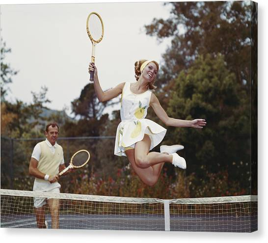 Couple On Tennis Court, Woman Jumping Canvas Print