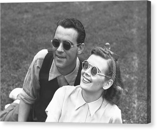 Couple Wearing Sunglasses Sitting On Canvas Print by George Marks