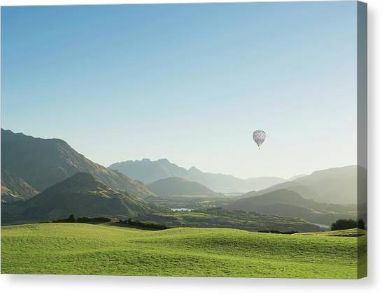 Hot Air Balloon Flying Above Rolling Canvas Print by Jacobs Stock Photography Ltd