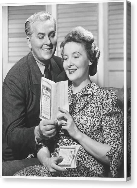 Mature Couple Looking At Brochure, B&w Canvas Print by George Marks