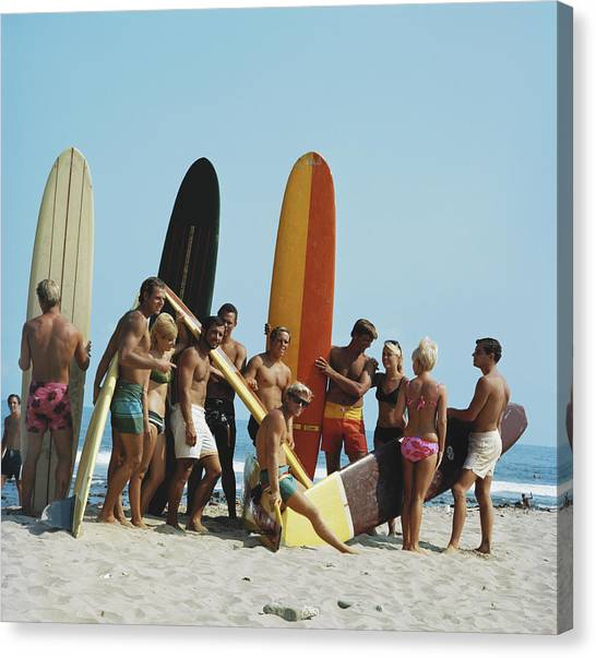 People On Beach With Surf Board Canvas Print