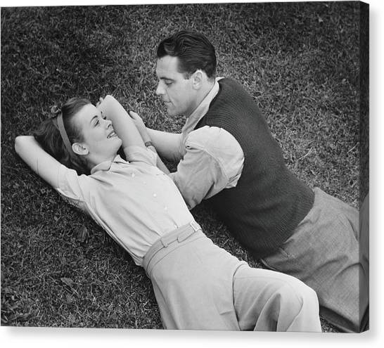 Romantic Couple Lying On Grass, B&w Canvas Print by George Marks