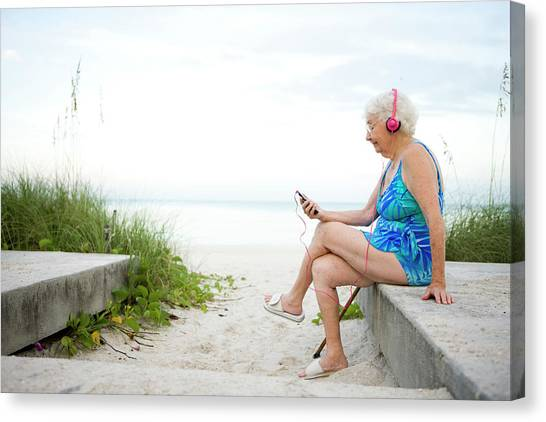 Senioir Woman Listening To An Mp3 Canvas Print