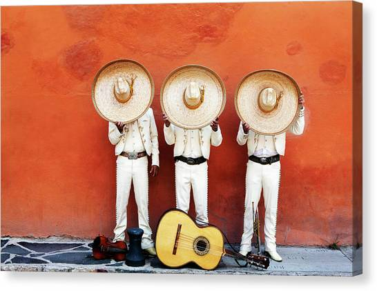 Three Mariachis On An Orange Wall Canvas Print