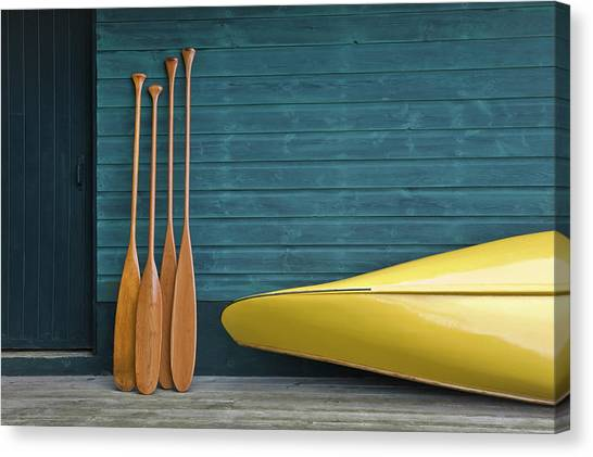 Yellow Canoe And Paddles On Dock Canvas Print by Mary Ellen Mcquay