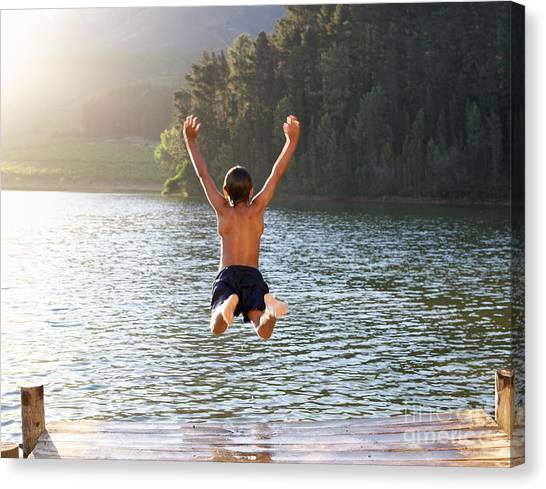 Exercising Canvas Print - Young Boy Jumping Into Lake by Monkey Business Images