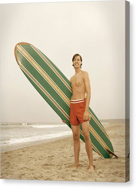 Young Man Carrying Surfboard On Beach Canvas Print