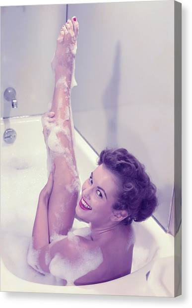 Young Woman In Bath Tub Lathering Canvas Print by Hulton Archive