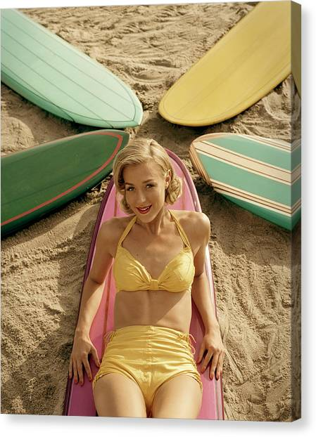Young Woman Lying On Surfboard On Sand Canvas Print