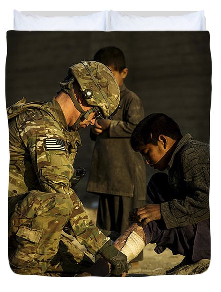 Airman Provides Medical Aid To A Local Duvet Cover by Stocktrek Images