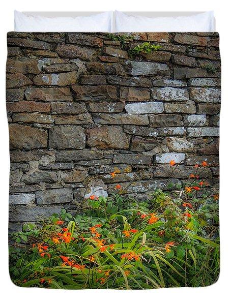 Orange Wildflowers Against Stone Wall Duvet Cover
