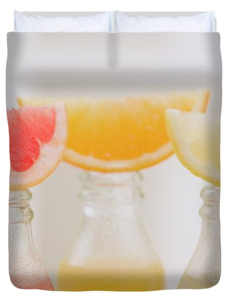 Three Fruit Juices In Bottles With Wedges Of Fresh Fruit Duvet Cover