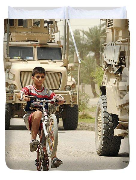 An Iraqi Boy Rides His Bike Past A U.s Duvet Cover by Stocktrek Images