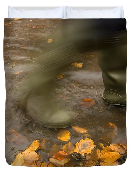 Person In Motion Walks Through Puddle Duvet Cover by John Short