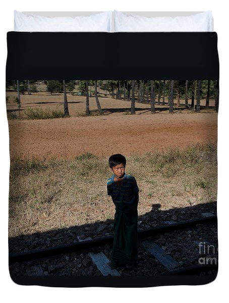 Duvet Cover featuring the photograph A Boy In Burma Looks Towards A Train From The Shadows by Jason Rosette