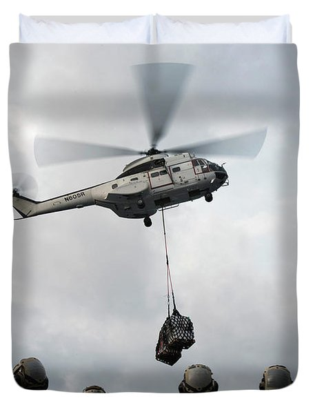 An As-332 Super Puma Helicopter Delivers Supplies To Uss Bonhomme Richard During A Replenishment-at- Duvet Cover