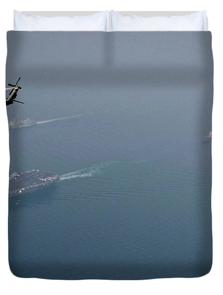 An Mh-60r Sea Hawk Helicopter  Flies Over The Aircraft Carrier Duvet Cover