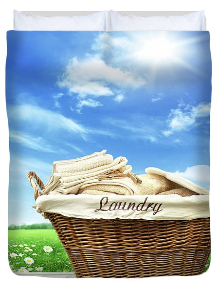 Laundry Basket With Clothes On Rustic Table Against Blue Sky Duvet Cover