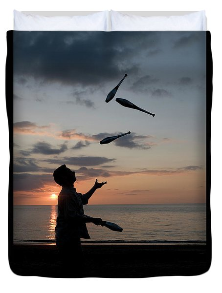 Man Juggling With Four Clubs At Sunset Duvet Cover