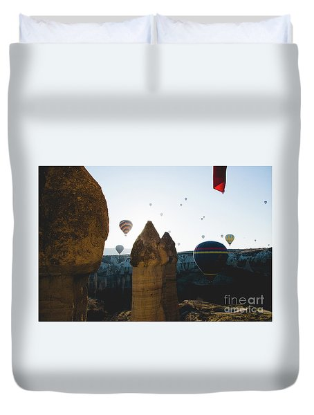 hot air balloons for tourists flying over rock formations at sunrise in the valley of Cappadocia. Duvet Cover