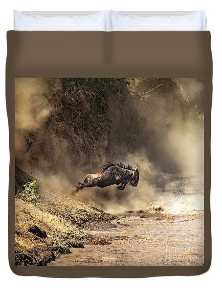 Wildebeest Leaps From The Bank Of The Mara River Duvet Cover