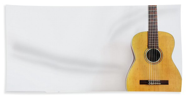 Acoustic Guitar On Piano Keyboard In Front Of White Wall. Hand Towel